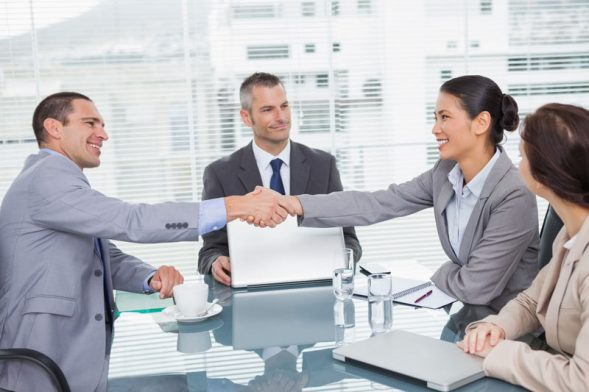 Business meeting with woman shaking man's hand across table